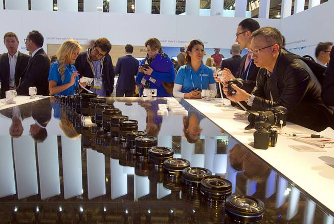 People look over the NX30 smart camera at the Samsung Electronics  booth during the 2014 International Consumer Electronics Show (CES) in Las Vegas, Tuesday Jan. 7, 2014.