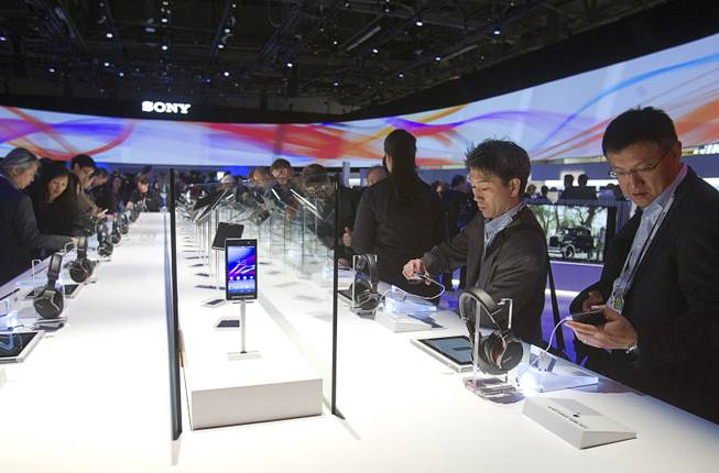 People look over headphones and Xperia Z1s smartphones at the Sony booth during the 2014 International Consumer Electronics Show (CES) in Las Vegas, Tuesday Jan. 7, 2014.