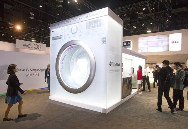 People pass by an oversize mockup of an LG Electronics washer at the LG booth during the 2014 International Consumer Electronics Show (CES) in Las Vegas, Tuesday Jan. 7, 2014.