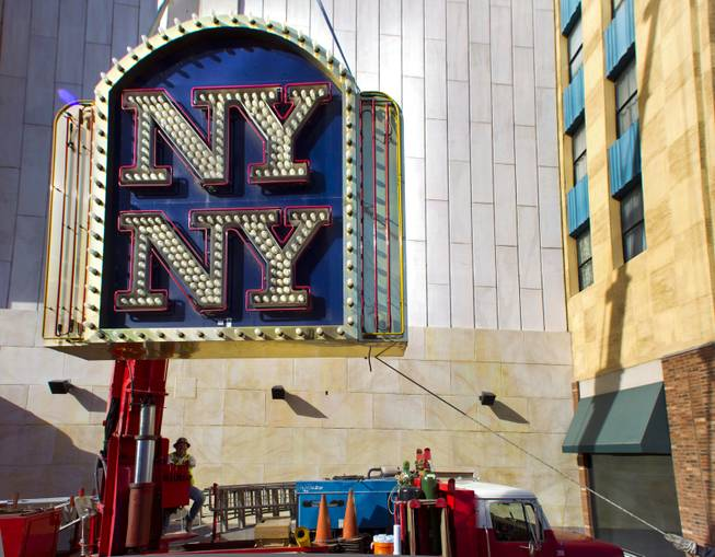 Yesco's Boyd Allen controls a crane with the New York - New York Hotel & Casino marquee entrance sign attached as it's taken down to be loaded on a flatbed and taken to the Neon Museum on Tuesday, Jan. 7, 2014.