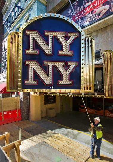 Yesco's Kent Faddi slowly steers the New York - New York Hotel & Casino marquee entrance sign as it's taken down  and donated to the Neon Museum on Tuesday, Jan. 7, 2014.