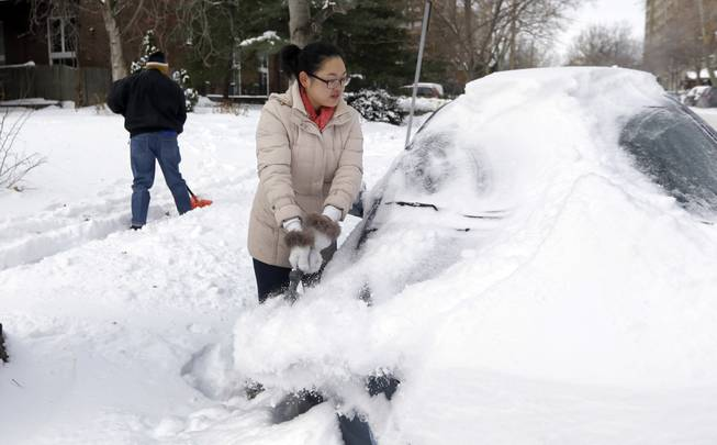 Cecy Wang, right, clears snow off her car as Samuel Scott, left, shovels a sidewalk Tuesday, Jan. 7, 2014, in St. Louis. As Missourians muddled through another frigid day Tuesday, the worst cold snap in nearly two decades was about to come to an end but many roads remained partly snow-covered two days after a winter storm dumped several inches of snow.