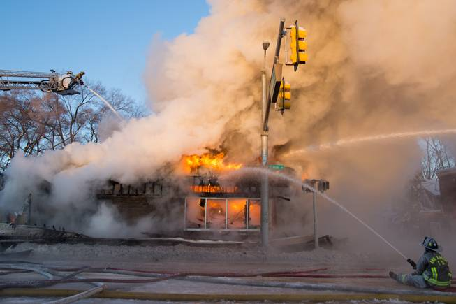 Ann Arbor firefighters battle a fire at Happy's Pizza in Ann Arbor, Mich., on Tuesday, Jan. 7, 2014.   Firefighters worked for several hours in temperatures that dipped to 15 degrees below zero to extinguish a blaze at the pizza shop. No injuries were reported following the fire.