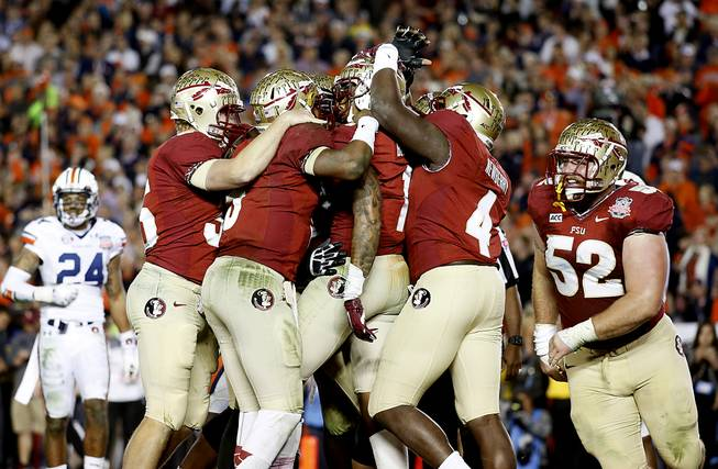 Florida State wide receiver Kelvin Benjamin (1) is surrounded by teammates after scoring the game-winning touchown against Auburn University in the 2014 BCS Championship NCAA College Football game on Monday, Jan. 6, 2014 in Pasadena, Calif. Florida State defeated Auburn 34-31.