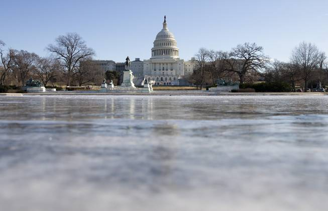 The reflecting pool in front of the U.S. Capitol building is frozen over, Tuesday, Jan. 7, 2014, in Washington.