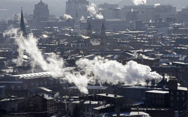 Steam rises from buildings Tuesday, Jan. 7, 2014, in downtown Cincinnati where temperatures were below zero in the morning.  Brutal, life-threatening cold descended over the East and the South, sending the mercury plummeting Tuesday into the single digits and teens.