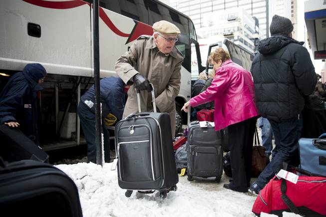 Passengers unload their luggage after arriving at Union Station after their Amtrak train from Los Angeles became stuck in snow drifts on Tuesday, Jan. 7, 2014, in Chicago. The severe weather forced hundreds of Amtrak passengers to spend the night onboard three trains stranded due to the snow in northern Illinois.