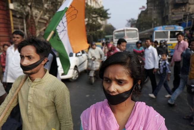 Activists of Indian National Congress with black bands around their mouths block traffic during a protest against a gang rape and murder of a 16-year-old girl at Madhyamgram, about 16 miles north of Kolkata in West Bengal, India, Jan. 3, 2014.