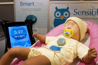 A SmartOne infant sleep monitor is shown on a doll at the Sensible Baby booth during the 2014 International Consumer Electronics Show (CES) in Las Vegas, Jan. 8, 2014. The wearable device, fits into a chest pocket, and sends information and active alerts on temperature, baby orientation and breathing to a parent's mobile device. The device will retail for $149.00 and be available online in the second quarter of 2014.
