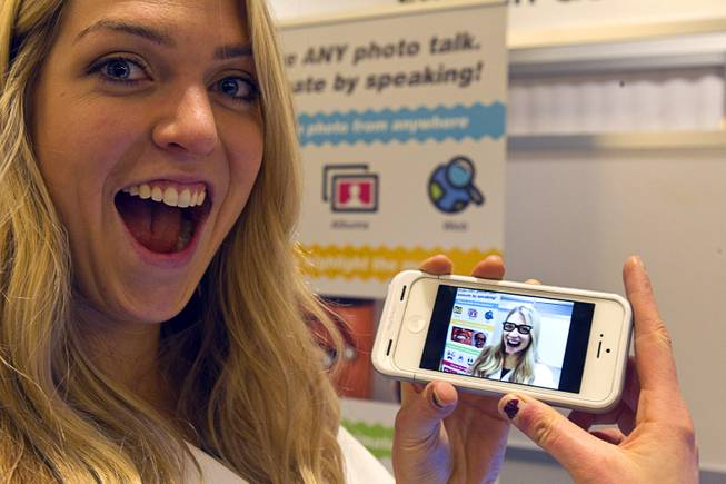 Gillian Pennington holds a smartphone with a animated, speaking image of herself in the Freak 'n Genius booth during the 2014 International Consumer Electronics Show (CES) in Las Vegas, Jan. 8, 2014. Using the YAKiT app, free download for iOS, a user can easily add talking animation to any photo.