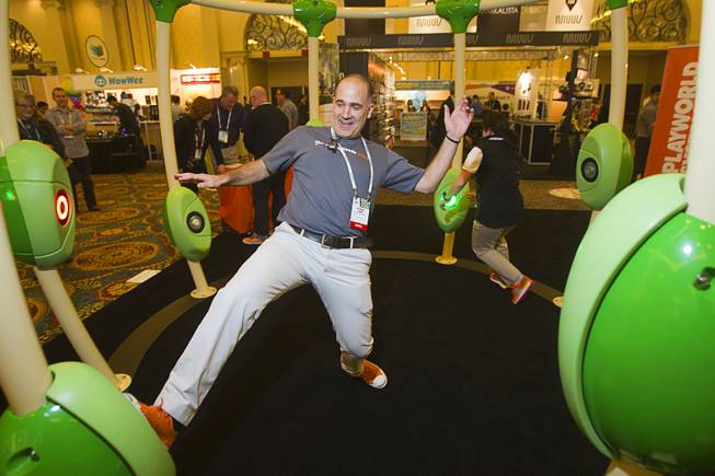 "Michael Laris (L) and Tracey Cassidy play the Neos 360  ""Light Grabber"" game by Playworld Systems during the 2014 International Consumer Electronics Show (CES) in Las Vegas, Jan. 8, 2014. The system is designed for schools, parks and public areas, Cassidy said."