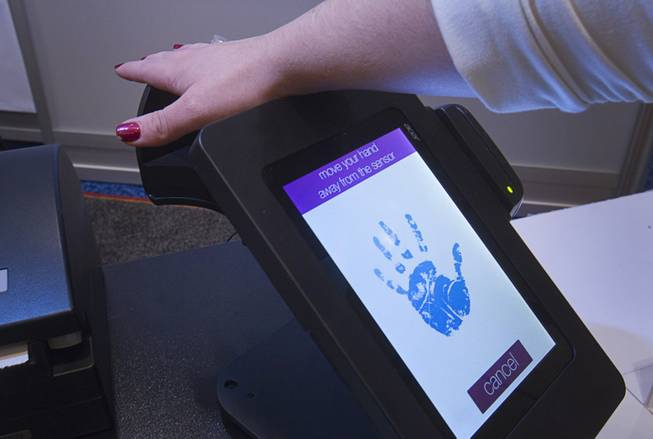 "A woman registers her palm on a PulseWallet, a point-of-purchase device, during the 2014 International Consumer Electronics Show (CES) in Las Vegas, Jan. 8, 2014. The system measures vein patterns in the palm. After confirming a person's identity, the purchase can be paid with a ""digital wallet"" linked to a credit card, debit card, a bank account or even paid in bit coins."