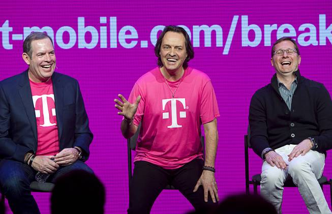 T-Mobile executives (L-R) CFO Braxton Carter, CEO John Legere, and CMO Mike Sievert, react to a question during a news conference at the 2014 International Consumer Electronics Show (CES) in Las Vegas, Jan. 8, 2014. T-Mobile announced it will pay Early Termination Fees (ETF) for families who transfer service from AT&T, Verizon, and Sprint.