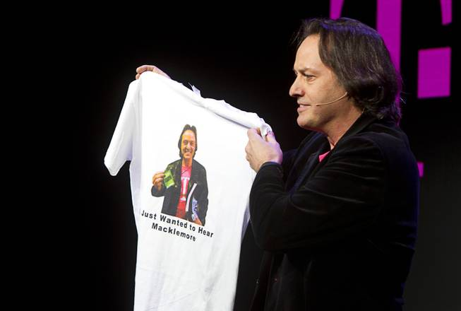 T-Mobile CEO John Legere  holds a custom-made T-shirt with his image during a news conference at the 2014 International Consumer Electronics Show (CES) in Las Vegas, Jan. 8, 2014. The shirt is a reference to Legere getting kicked out of a AT&T-sponsored party featuring a performance by Macklemore.