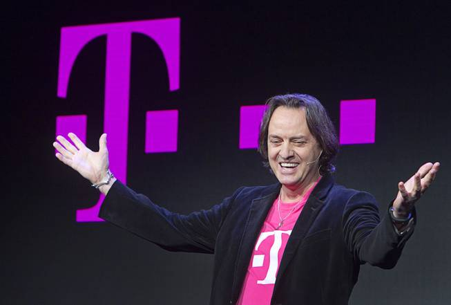 T-Mobile CEO John Legere speaks during a news conference at the 2014 International Consumer Electronics Show (CES) in Las Vegas, Jan. 8, 2014. T-Mobile announced they will pay Early Termination Fees (ETF) for families who transfer service from AT&T, Verizon, and Sprint.