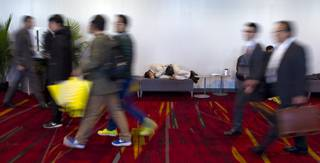 An attendee at CES takes a nap outside of a showroom within the Las Vegas Convention Center on Wednesday, Jan. 8, 2014.