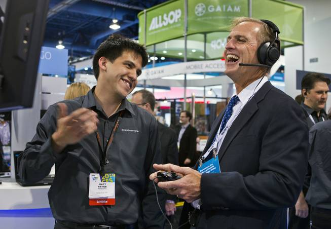 (from left) Matt Payne shows Don Houston of Plantronics some of the great new technology they have produced in their display at CES within the Las Vegas Convention Center on Wednesday, Jan. 8, 2014.