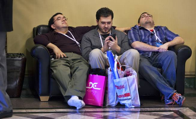 (From left) Erwin,  Sean and Jonathan Quinonez of West Jordan, Utah, do their best to relax after a long day of CES at the Las Vegas Convention Center on Wednesday, Jan. 8, 2014.
