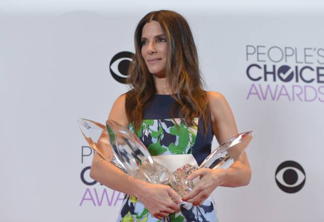 Sandra Bullock, winner of the Favorite Movie Actress, Favorite Dramatic Movie Actress and Favorite Comedic Movie Actress poses in the press room at the 40th annual People's Choice Awards at Nokia Theatre L.A. Live on Wednesday, Jan. 8, 2014, in Los Angeles.