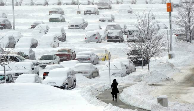 A woman walks back to her car in the long term parking lot at Indianapolis International Airport, Monday Jan. 6, 2014.