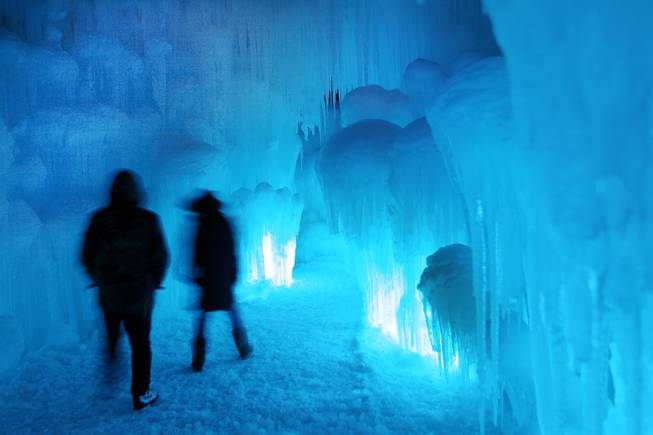In this photo taken Wednesday Jan. 8, 2014 patrons tour an ice castle at the base of the Loon Mountain ski resort in Lincoln, N.H. The ice castle begins to grow in the fall when the weather gets below freezing and thousands of icicles are made and harvested then placed around sprinkler heads and sprayed with water.  The castle will continue to grow as long as the temperatures stay below freezing.