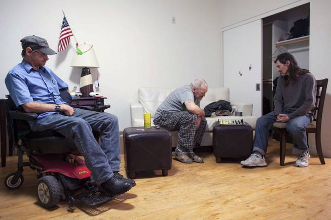 John Hankins, right, who repaired ballistic missiles for the Air Force, plays chess with William Godwin as Gary Workman, left, watches, in Phoenix, Jan. 8, 2014. All three veterans were considered chronically homeless but now live in Victory Place, apartments subsidized by the city government in Phoenix, which believes there are no more former servicemen living on its streets.
