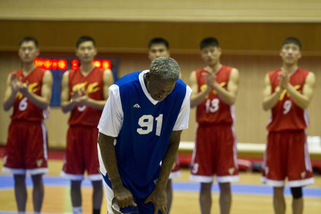 Dennis Rodman bows to North Korean leader Kim Jong Un, seated above in the stands, after singing Happy Birthday to Kim before an exhibition basketball game with U.S. and North Korean players at an indoor stadium in Pyongyang, North Korea on Wednesday, Jan. 8, 2014.