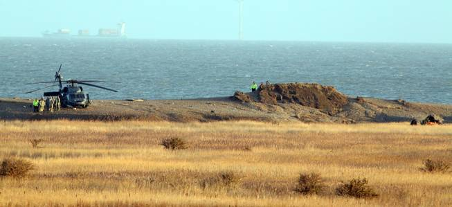 The wreckage of a U.S. Military Air Force Pave Hawk helicopter, at right, lies on the ground in Salthouse, England, on Wednesday Jan. 8, 2014. The Pave Hawk helicopter slammed into the eastern coast during a low-level training mission Tuesday evening. Authorities cordoned off flooded marshes Wednesday to remove the bodies of four U.S. Air Force crewmen that were killed in the crash.