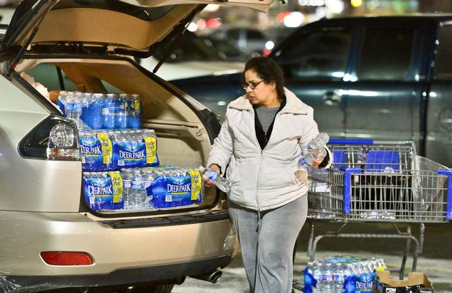 Charleston resident Niru Parikshak loads up the back of her car with bottled water Thursday Jan. 9, 2014, in Charleston, W.Va. Sam's Club and every retailer for a 20-mile radius sold out of bottled water after a chemical leak Thursday morning up river from the WV American Plant on the Elk River forced the water plant to shut down.