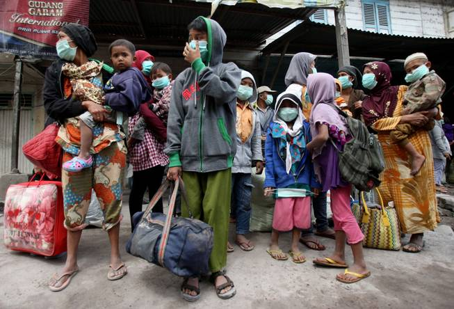 Villagers wait for the bus as they flee their homes following the eruption of Mount Sinabung in Payung, North Sumatra, Indonesia, Wednesday, Jan. 8, 2014.
