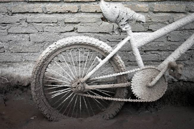 A bicycle is caked with volcanic ash from the eruption of Mount Sinabung outside a house in Sibintun, North Sumatra, Indonesia, Tuesday, Jan. 7, 2014.