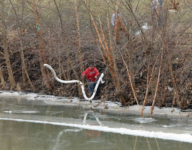 A Freedom Industries worker places a boom in the Elk River Thursday, Jan. 9, 2014, at the site of a chemical leak in Charleston that has fouled the drinking water in five West Virginia counties.