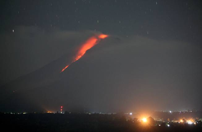 In this photo made with a slow shutter speed, hot lava flows from the crater of Mount Sinabung as seen from Gundaling, North Sumatra, Indonesia, early Thursday, Jan. 9, 2014. The volcano has sporadically erupted since September, forcing thousands of people who live around it slopes to flee their homes.