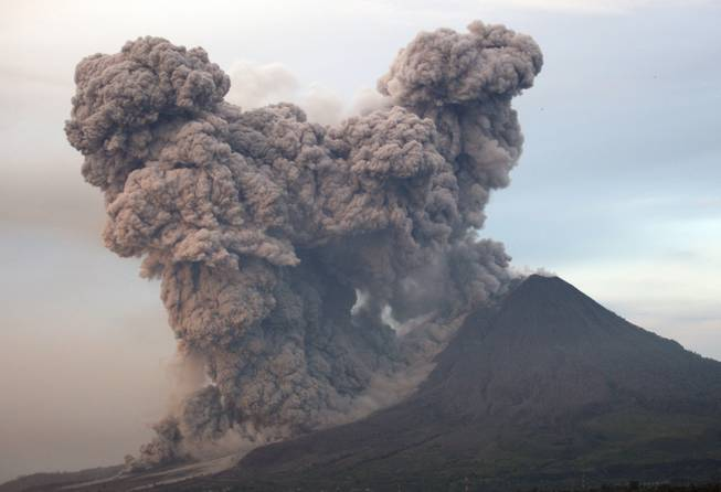 Mount Sinabung spews volcanic materials as seen from Gundaling, North Sumatra, Indonesia, Wednesday, Jan. 8, 2014. The volcano has sporadically erupted since September, forcing thousands of people who live around it slopes to flee their homes.