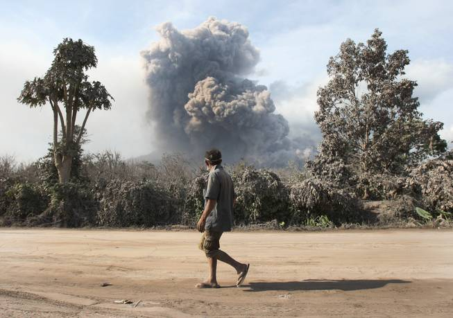 A man watches as Mount Sinabung spews volcanic materials in Sibintun, North Sumatra, Indonesia, Wednesday, Jan. 8, 2014. The volcano has sporadically erupted since September, forcing thousands of people who live around it slopes to flee their homes.