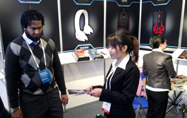 Lei Zhang of Shenzhen Suoai Electronics and Technology, Shenzhen, China, gives product literature to a customer at her 2014 CES booth Wednesday, Jan. 8, 2014, at the Venetian.