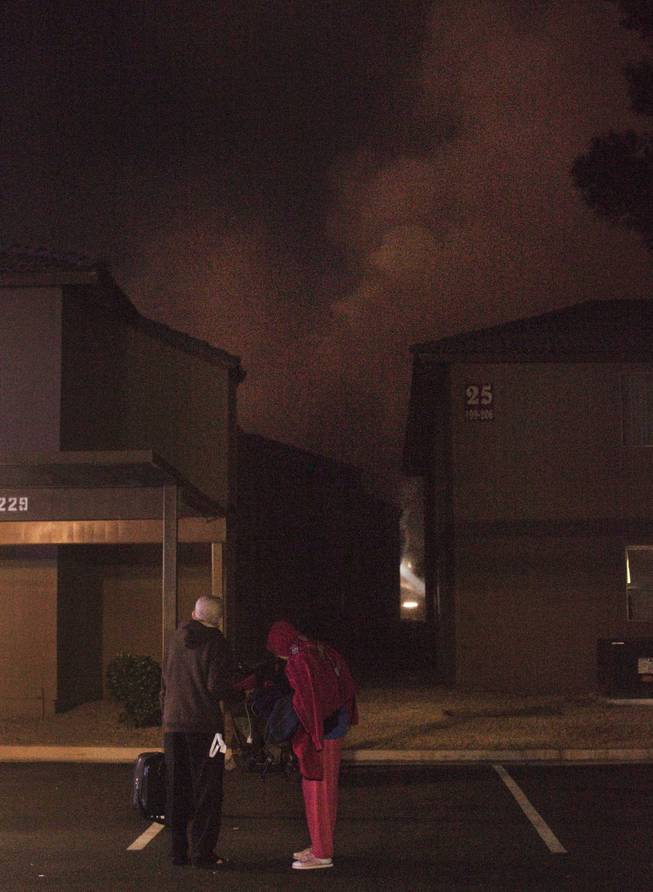 Century Village apartments residents Freddie Veloro and his wife, Tessie, carry some of their belongings as smoke from a fire billows in the background. Clark County firefighters responded to a blaze at the apartment complex early Thursday, Jan. 9, 2014.