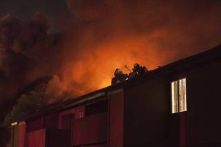 Firefighters on the roof of Century Village apartments, 4801 Spencer St., early Thursday Jan. 9, 2014.