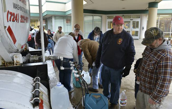 David Fletcher, center, a member of the Belle Fire Department, took off a day of work at his accounting job for the state so he could help distribute water at Riverside High School in Charleston, W.Va., after a chemical spill in the Elk River in Charleston shut down much of the city and surrounding counties, Friday Jan 10, 2014.  He said that earlier he dropped off some water for some of his elderly neighbors.