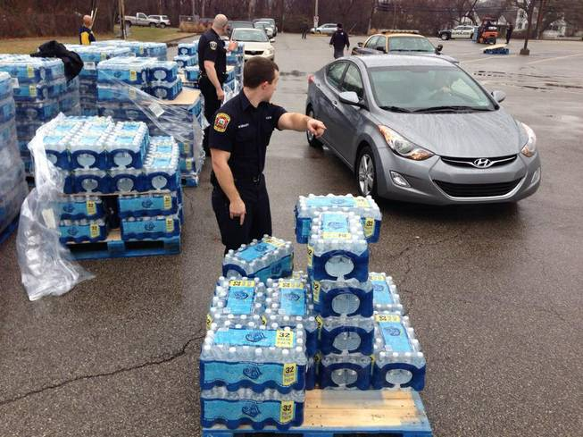 City officials help direct traffic through a water distribution site set up at the South Charleston Recreation Center in South Charleston, W.Va., Friday, Jan. 10, 2014, after at least 100,000 customers in nine West Virginia counties were told not to drink, bathe, cook or wash clothes using their tap water because of a chemical spill into the Elk River in Charleston, with Gov. Earl Ray Tomblin declaring a state of emergency Thursday for all those areas. The site opened before 9 a.m. with bottled water and a tanker truck, but  was expected to run out of water about 90 minutes later.