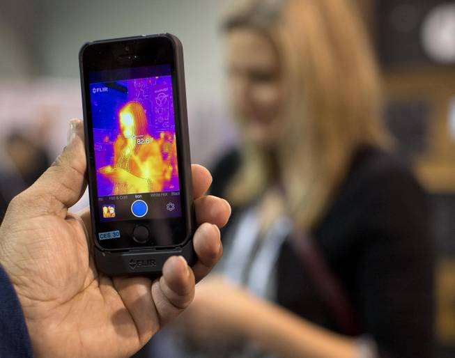 The FLIR ONE thermal imager for the iPhone is demonstrated at the International Consumer Electronics Show, Thursday, Jan. 9, 2014, in Las Vegas. The imager attaches to the back of an iPhone 5 or 5s and translates heat data into color images on the phone's screen.