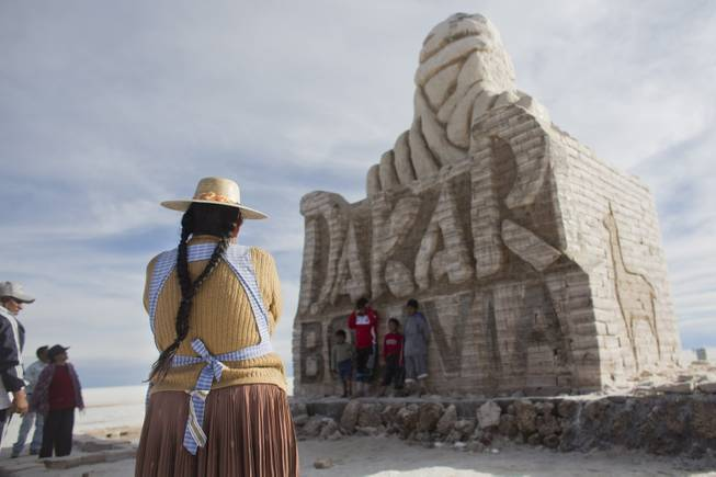 An Aymara Indigenous woman looks at a monument made of salt to welcome the Dakar Rally at the Uyuni Salt Flats in Uyuni, Bolivia,  Saturday, Jan. 11, 2014. Dakar rally Motorcycles and quads will race through parts of the Uyuni Salt Flats on Jan. 13, 2014.
