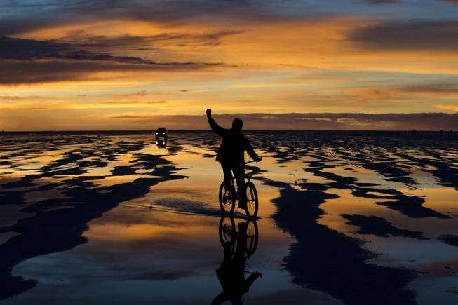 A bicycle rider waves to friends at the Uyuni Salt Flats in Uyuni, Bolivia,  Saturday, Jan. 11, 2014. The motorcycles and quads of the Dakar Rally will race through parts of the Uyuni Salt Flats on Jan. 13, 2014.
