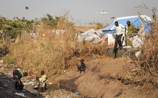 Young displaced children wash their clothes in a stream of fetid water that runs through a camp for people who have fled the recent violence, as a United Nations helicopter flies overhead in the distance, in the capital Juba, South Sudan Saturday, Jan. 11, 2014. South Sudanese government troops on Friday retook Bentiu, the capital of oil-producing Unity state, from rebels loyal to the country's former vice president, a military spokesman said, while hundreds of thousands remain displaced in the nearly monthlong conflict.