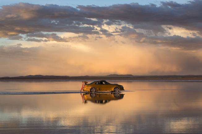 The sky is reflected on the Uyuni Salt Flats as a car drives by in Uyuni, Bolivia,  Saturday, Jan. 11, 2014. The motorcycles and quads of the Dakar Rally will race through parts of the Uyuni Salt Flats on Jan. 13, 2014.