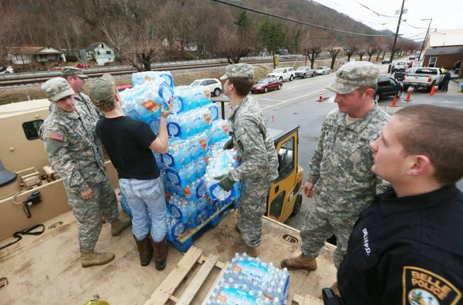 Members of the West Virginia Army National Guard, along with a member of the Belle Police Department and a volunteer, offload emergency water from a military truck to a forklift as citizens line up for water at the Belle Fire Department, Saturday, Jan. 11, 2014, in Belle, W.Va.