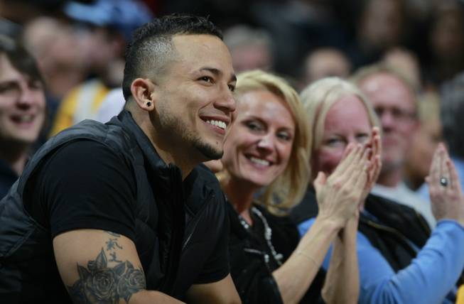 Colorado Rockies outfielder Carlos Gonzalez smiles as the crowd applauds as he is introduced in the fourth quarter while sitting courtside to watch the Miami Heat's 97-94 victory over the Denver Nuggets in an NBA basketball game in Denver on Monday, Dec. 30, 2013.