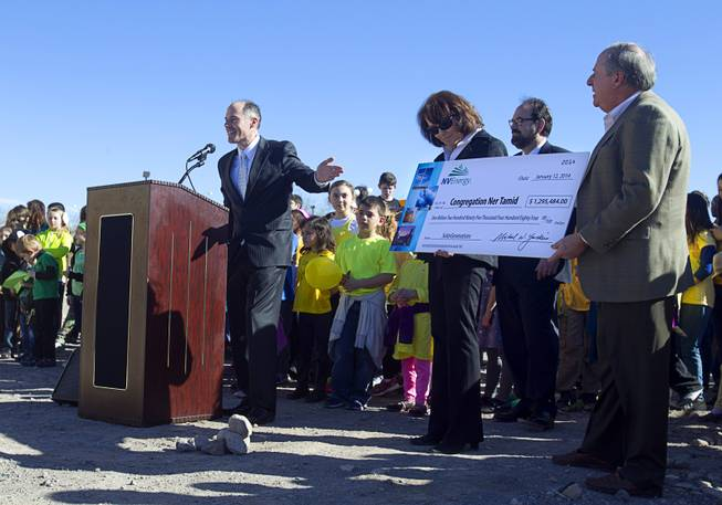 "Ben Robertson, left, coordinator for NV Energy's renewable generations program, presents a ceremonial rebate check to members of Congregation Ner Tamid during a news conference to ""unveil"" a solar photovoltaic field at the temple in Henderson Sunday, Jan. 12, 2014. The $1.6 million project, a partnership of Congregation Ner Tamid, NV Energy and Hamilton Solar, will produce about 75 percent of the temple's power usage on average, said Matthew Weinberger, Hamilton Solar's director of business development."