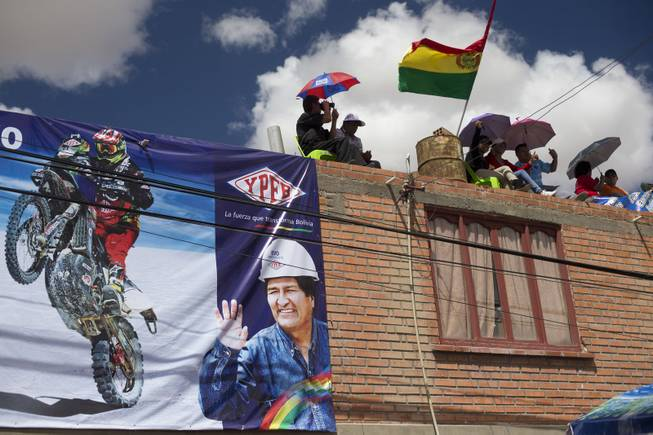 A poster with a photo of Bolivian President Evo Morales to promote Bolivia's state oil company decorates a building where people wait to see the motorcycles arriving at the end of the seventh stage of the Dakar Rally in Uyuni, Bolivia, Sunday, Jan. 12, 2014.