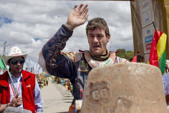 KTM rider Marc Coma of Spain waves as he arrives at the end of the seventh stage of the Dakar Rally in Uyuni, Bolivia, Sunday, Jan. 12, 2014.